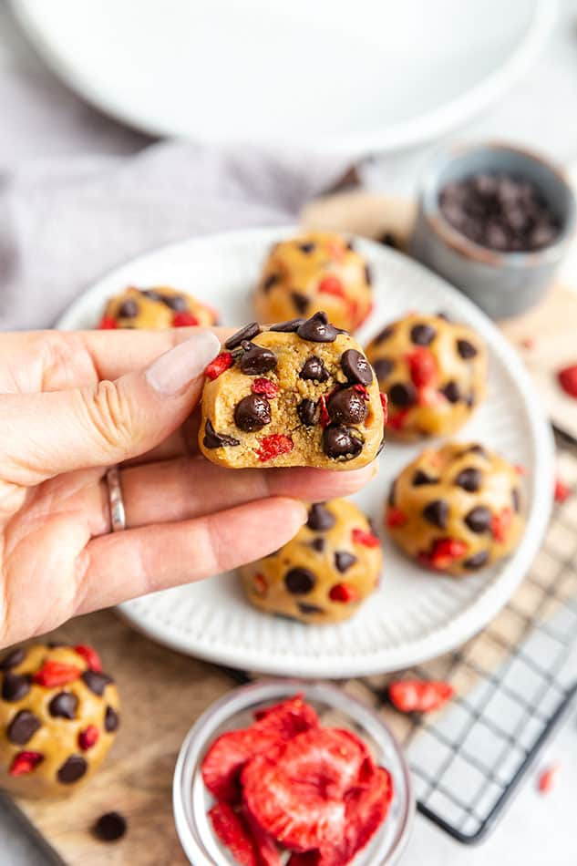 A hand holding a Strawberry Protein Ball with chocolate chips