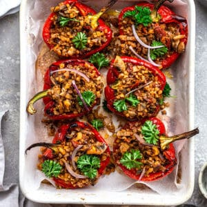 Top view of vegan stuffed peppers with parsley in a white baking dish on a grey background