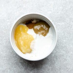 Top view of ingredients to make keto paleo mug cake batter in a white mug