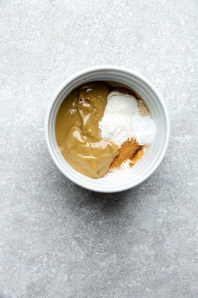 Top view of ketoTop view of ingredients to make keto paleo mug cake batter in a white mug mug cake batter in a white mug