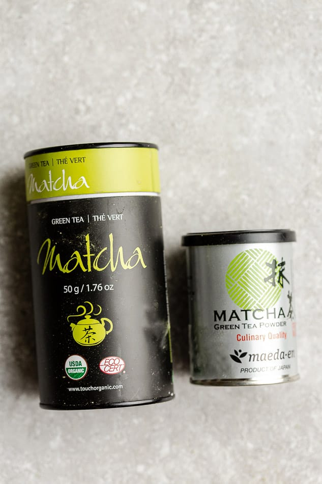 Overhead image of matcha containers on grey surface.