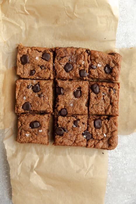 Top view of 9 soft and chewy vegan chocolate chip cookie bars on a brown parchment paper