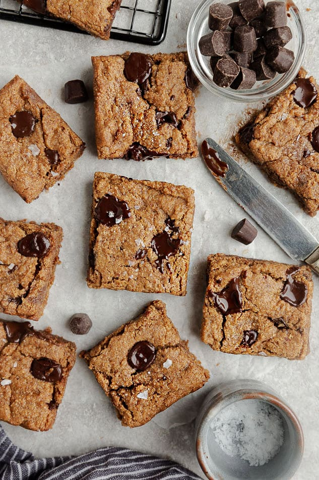 Squares of chocolate chip cookie bars garnished with chocolate and salt.