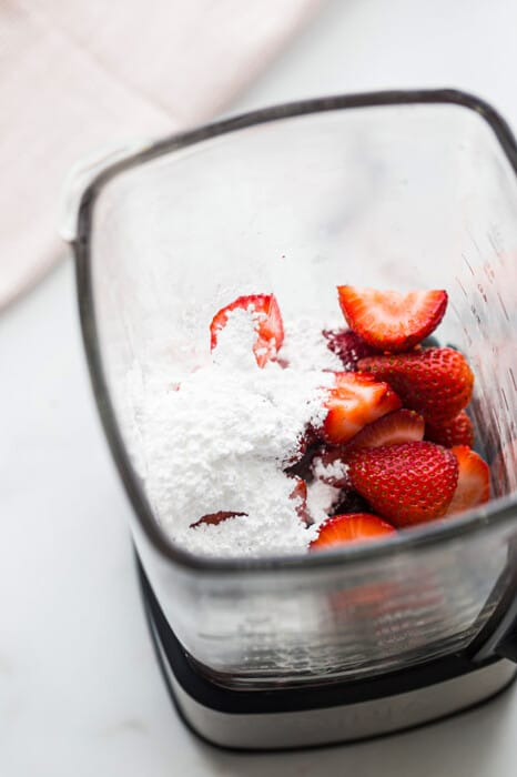 Top view of strawberries and coconut cream in a blender