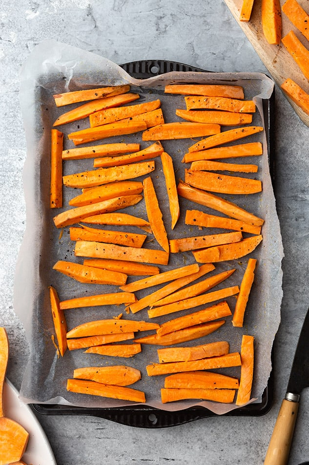 Top view of sliced sweet potatoes on a baking sheet