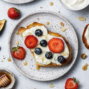 One slice of whipped ricotta toast with sliced strawberries and blueberries on a white plate