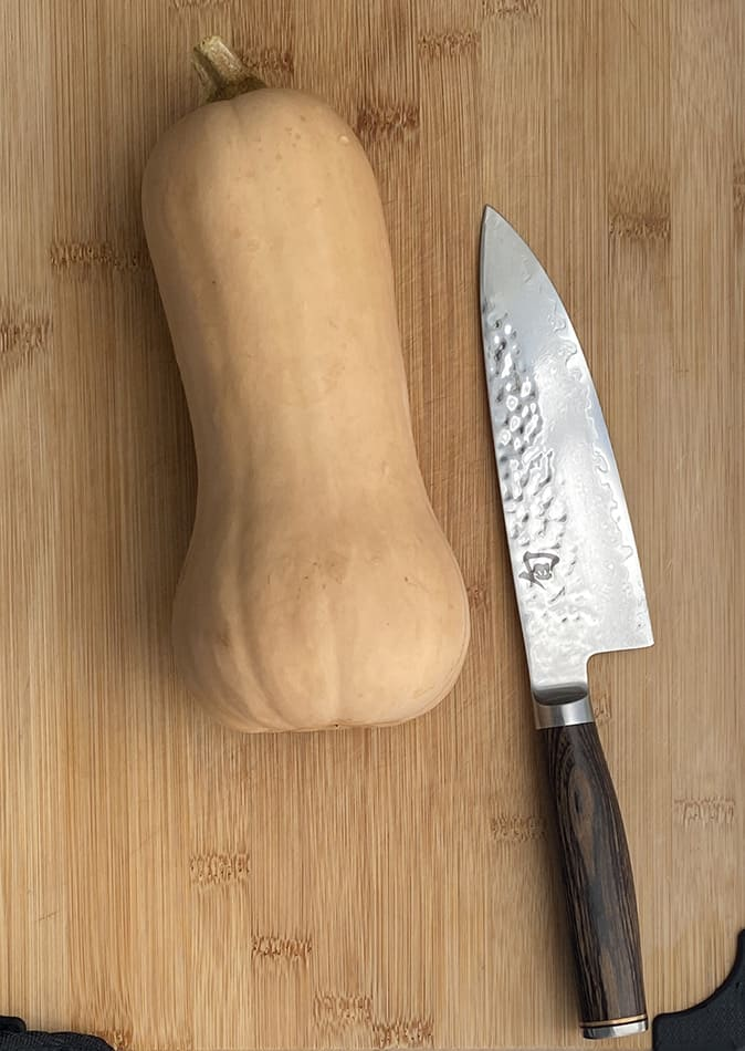 A whole butternut squash next to a chef's knife on a wooden cutting board