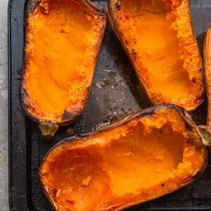 Overhead view of several roasted halves of butternut squash on a metal pan