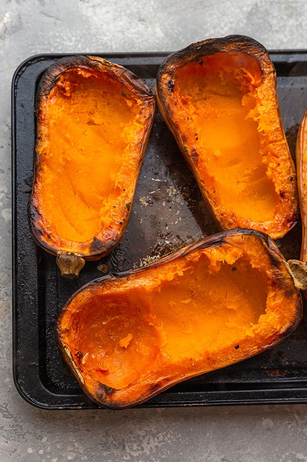 Several roasted halves of butternut squash on a metal baking sheet