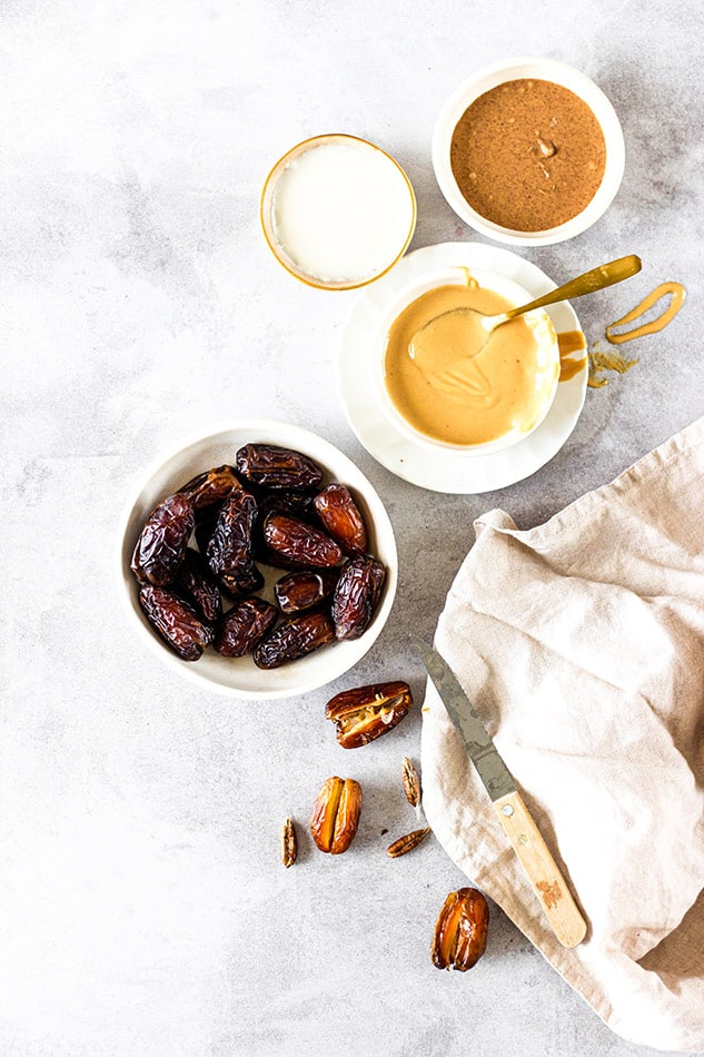 Close-up view of ingredients for making stuffed dates on a grey background
