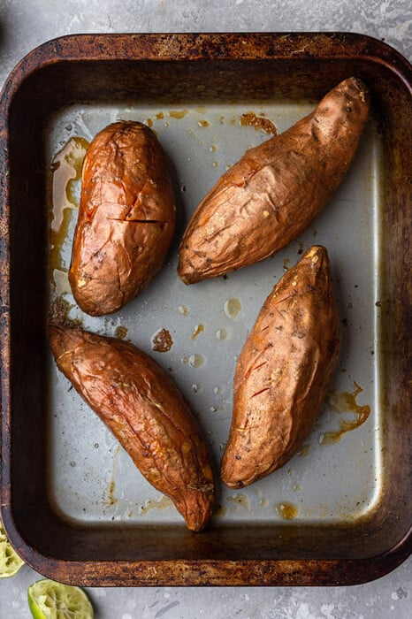 Four Sweet Potatoes Coated in Oil in a Metal Pan