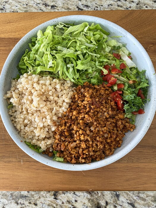 Building a vegan taco bowl with lettuce, cauliflower rice, pico and walnut taco filling