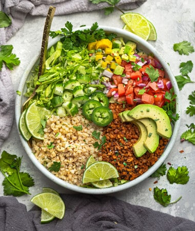 Top view of a loaded vegan taco bowl on a grey background with a gold fork