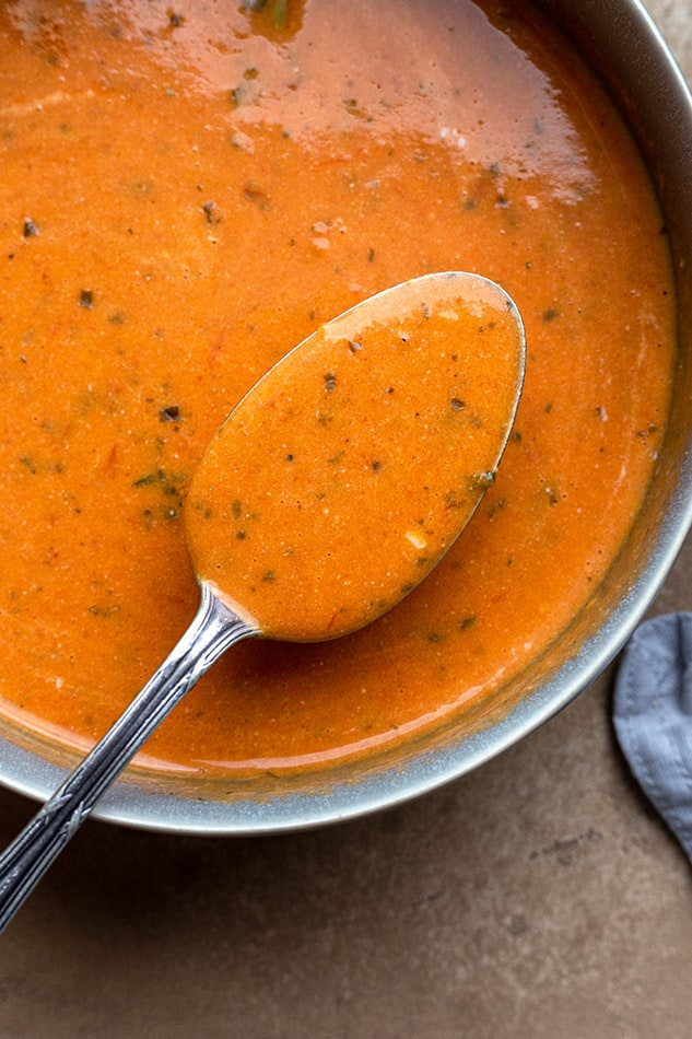 Close-up view of vegan tomato soup in a pot with a spoon