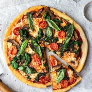 Top view of a whole vegetable pizza with one slice cut on parchment paper with a wooden knife