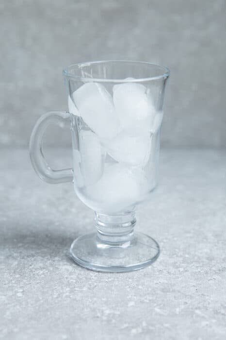 Image of clear glass filled with ice cubes on grey surface.