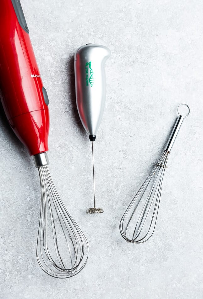 Overhead image of silver blender and red whisk tools on grey surface.