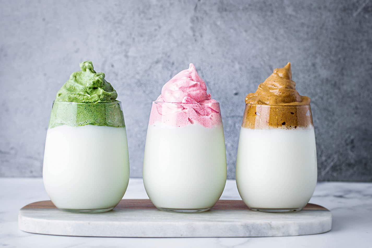 3 glasses filled with milk and whipped matcha, strawberry, and coffee on marble and grey surface.