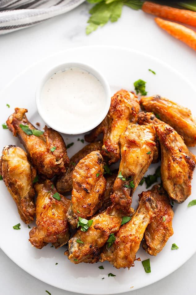 Overhead view of crispy Air Fryer Chicken Wings on a white plate with a cup of creamy dipping sauce