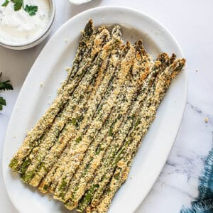 Top view of asparagus fries in a white oval dish