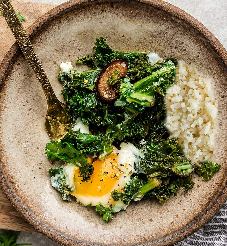 Overhead image of green shakshuka with cremini mushrooms and kale.