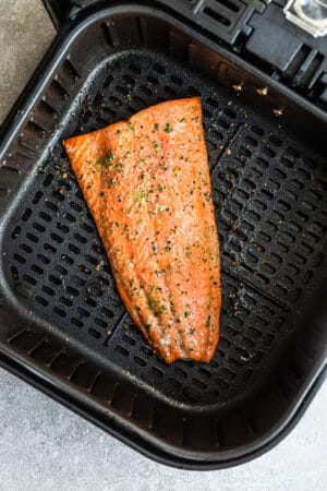 Top view of one large salmon fillet in the air fryer basket