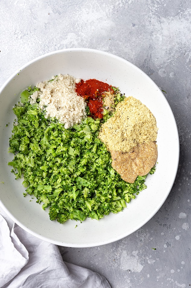 Top view of chopped broccoli and spices on a white plate to make low carb broccoli fritters
