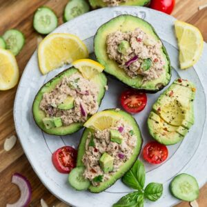 Top view of avocado tuna salad stuffed into 3 avocados on a white plate on a wooden board