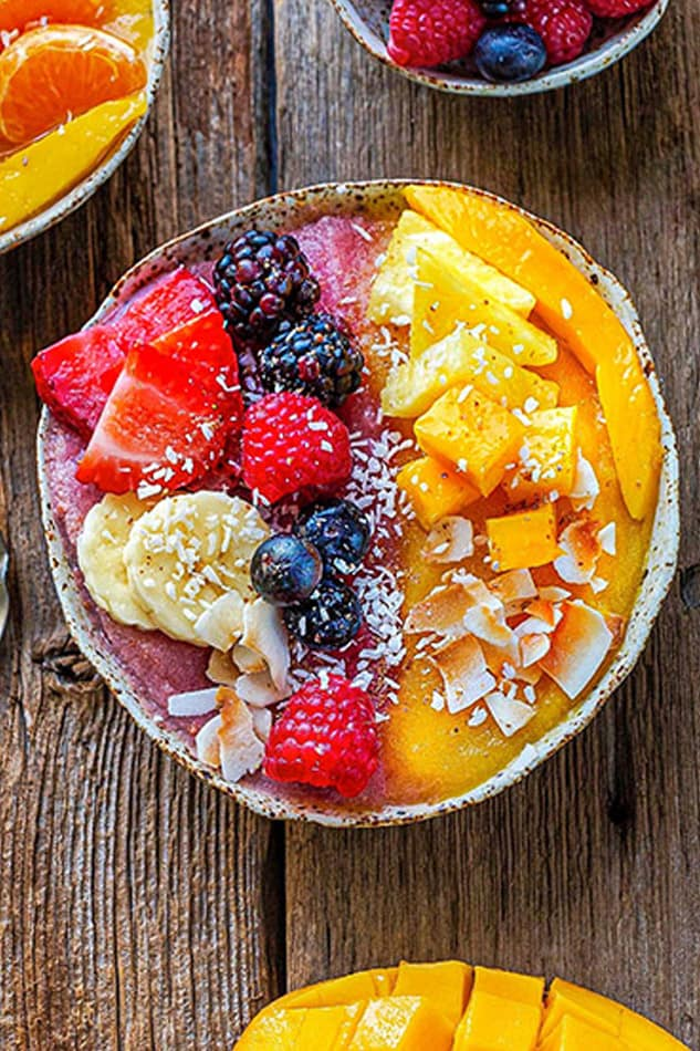 Close-up top view of an easy mango smoothie recipe in a white bowl topped with fresh berries and a spoon