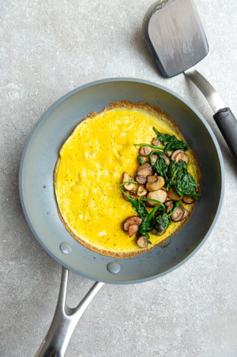 Top view of a cooked omelette on a grey nonstick skillet
