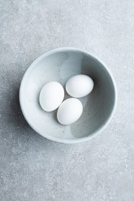 Top view of 3 large whole eggs in a white bowl