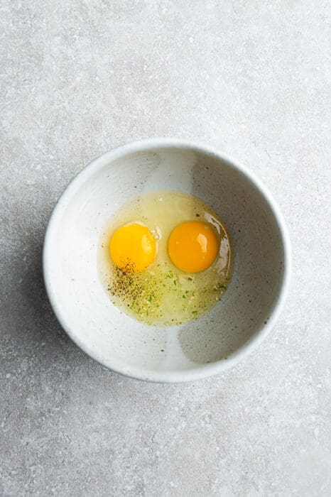 Top view of raw eggs in a white bowl with a whisk