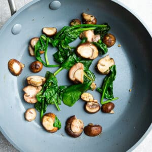 Top view of spinach and mushrooms on a grey nonstick skillet