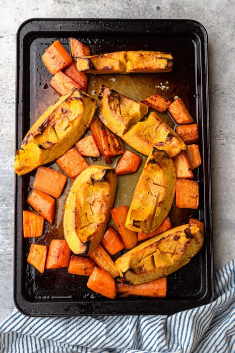 Roasted Pumpkins and Carrots Spread Across a Baking Sheet