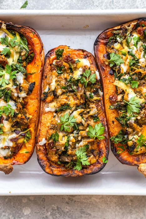 Overhead view of three stuffed butternut squash halves in a baking dish