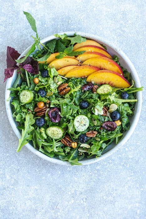Top view of arugula salad with peaches and blueberries in a white bowl on a grey background