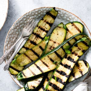 Top view of grilled zucchini slices on white plate with two forks.