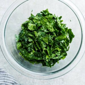 Top view of chopped kale in a clear bowl on a grey background