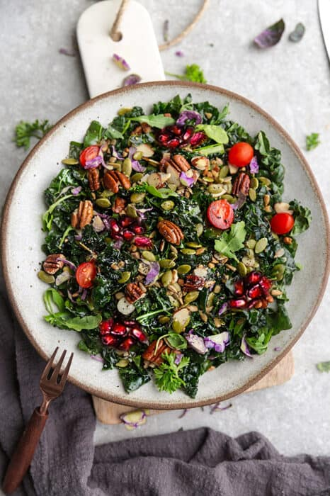 Top view of winter salad with kale in a white bowl on a grey background
