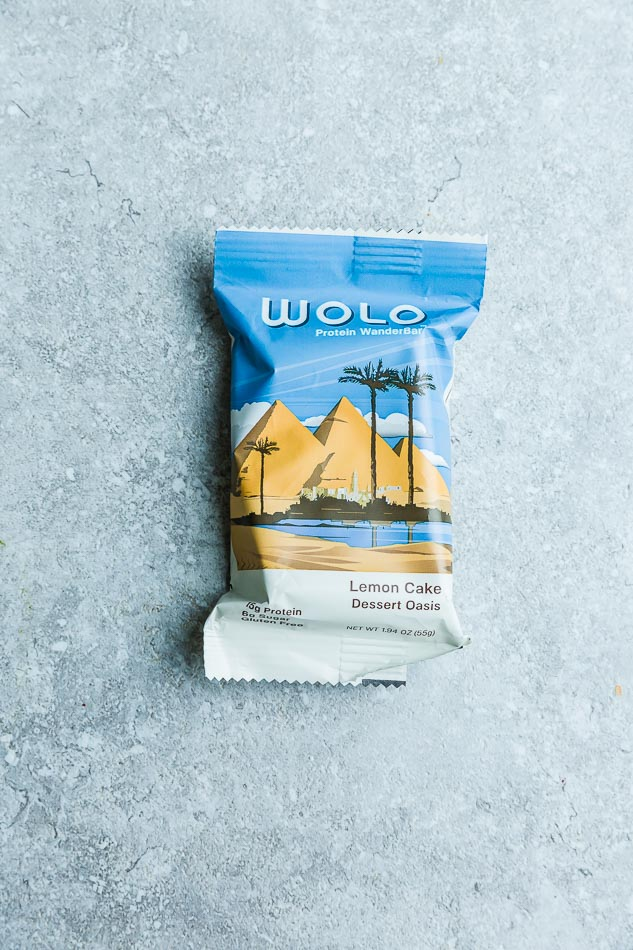WOLO Lemon Cake protein bar on a gray background