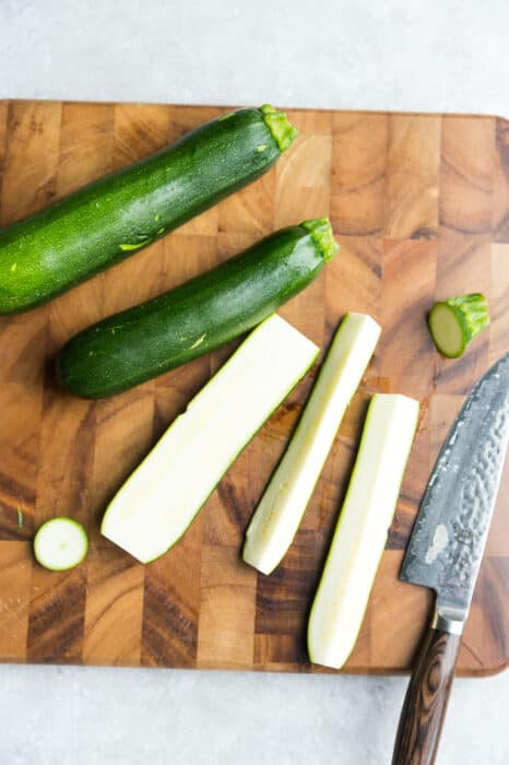 Top view of uncooked zucchini pieces on a wooden cutting board with a knife