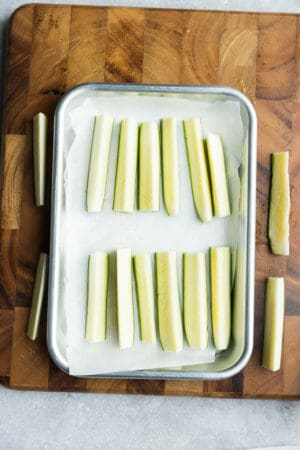 Top view of uncooked zucchini pieces on a baking sheet on a wooden cutting board