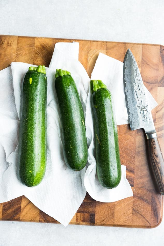 Top view of 3 zucchini on a cutting board with a knife