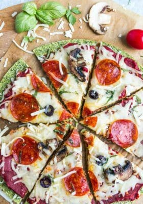 Top view of sliced baked zucchini Pizza Crust with tomato sauce, cheese, mushrooms, olives and pepperoni on brown parchment paper on a baking sheet