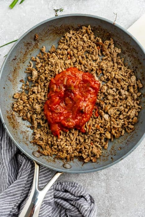 Top view of cooked ground turkey with salsa in a nonstick skillet