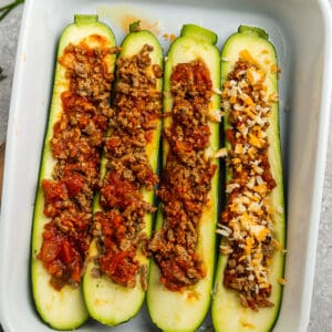 Top view of raw zucchini boats with cooked turkey taco filling and cheese in a white casserole dish