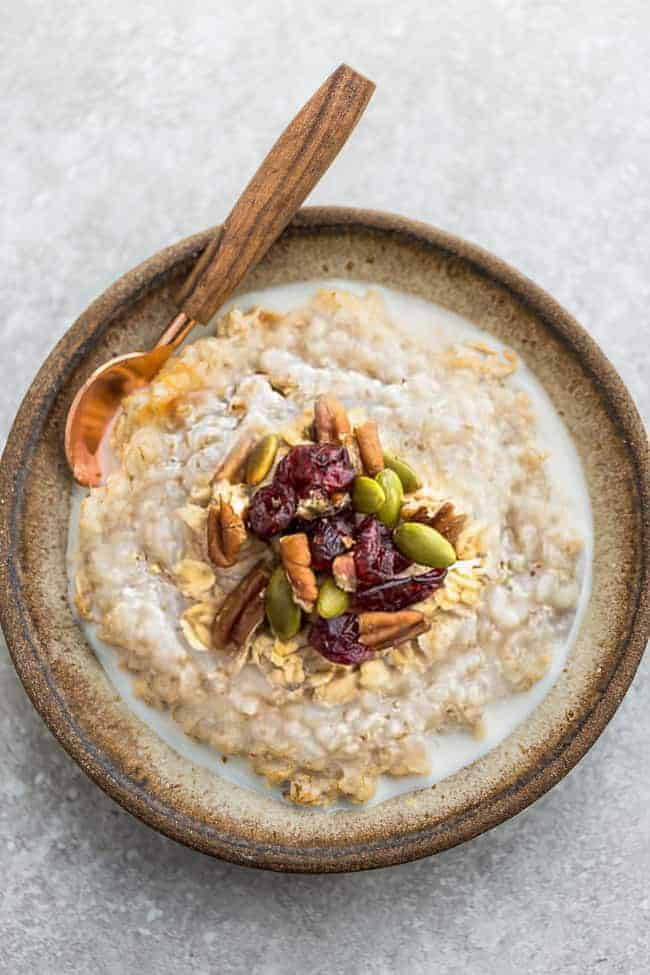 Overhead image of pumpkin steel cut oatmeal with nuts and dried fruit