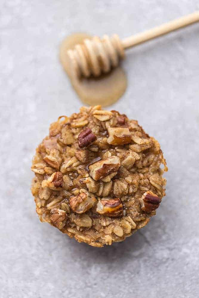 Overhead image of honey nut baked oatmeal cups with honey and oats.