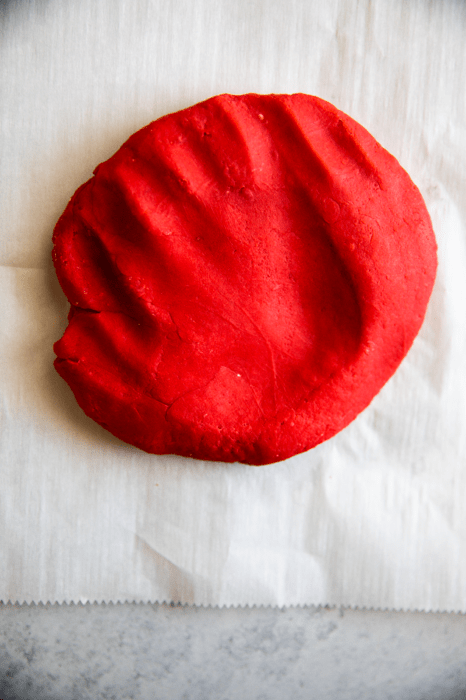 image of red homemade playdough without cream of tartar cooling off on wax paper