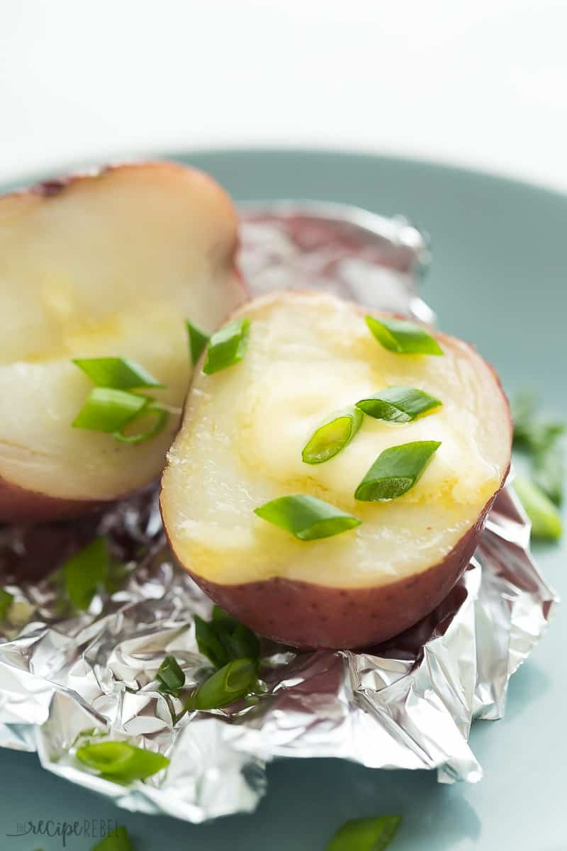 Two halves of an Instant Pot Baked Potato on foil with butter and scallions